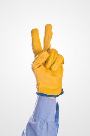 career timing: Construction Engineer Wearing Yellow Leather Protective Gloves  Raised Two Fingers for V sign or Voting, isolated on white background Stock Photo