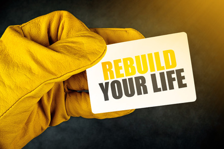 superintendent: Rebuild Your Life on Business Card, Male Hand in Yellow Leather Construction Working Protective Gloves Holding Card with Rounded Corners.