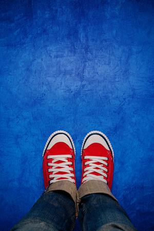 adulthood: Feet From Above Concept, Teenage Person in Red Sneakers Standing on Blue Background, Blank Copy Space in Front, Top View