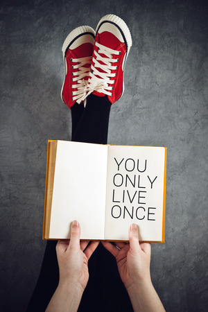 once: You Only Live Once or YOLO Concept with Young Woman Reading Book with Her Feet Raised in The Air