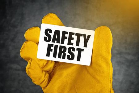 Bezpečnost na prvním místě na vizitku, Muž Ruku v žluté kůže Výstavba Ochranné pracovní rukavice drží karty se zaoblenými rohy.