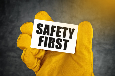 safety first: Safety First on Business Card, Male Hand in Yellow Leather Construction Working Protective Gloves Holding Card with Rounded Corners.