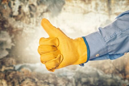 permission: Construction Engineer Wearing Yellow Leather Protective Gloves Gesturing Thumbs Up for Approval Stock Photo
