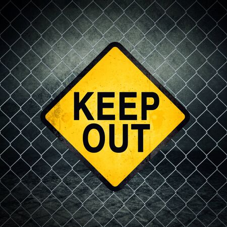 Keep Out Grunge Yellow Warning Sign on Chainlink Fence of Industrial Warehouse photo