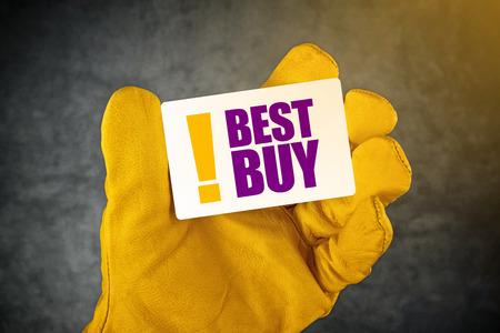endorse: Male Hand in Yellow Leather Construction Working Protective Gloves Holding Best Buy Card as Shopping Recommendation Concept.