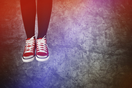 boyhood: Careless Young Teenage Woman Jumping for Joy, Red Sneakers on grunge Background Stock Photo