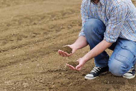 tierra fertil: Granjero de sexo masculino examina la calidad del suelo en la f�rtil tierra agr�cola Granja, Agr�nomo Comprobaci�n del suelo en manos.