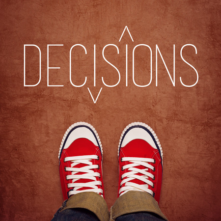 Youth Decision Making Concept, Feet in Red Sneakers from Above Standing at Ground with Decisons Title Printed, Top View Stock Photo