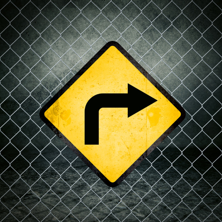 chainlink: Right Direction Grunge Yellow Warning Sign on Chainlink Fence of Industrial Warehouse