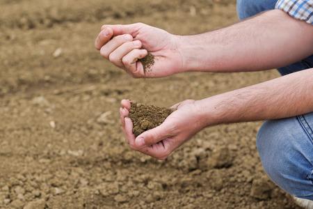 Mannelijke landbouwer onderzoekt bodemkwaliteit op vruchtbaar landbouwgebied Farm Land, Agronomist controleren Bodem in handen.