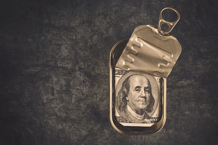 sardine can: Hundred American Dollar Bill in Open Empty Sardine Fish Tin Can on Grunge Gray Background, Top View