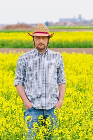 rappi: Male Farmer Standing in Oilseed Rapeseed Cultivated Agricultural Field Examining and Controlling The Growth of Plants, Crop Protection Agrotech Concept.