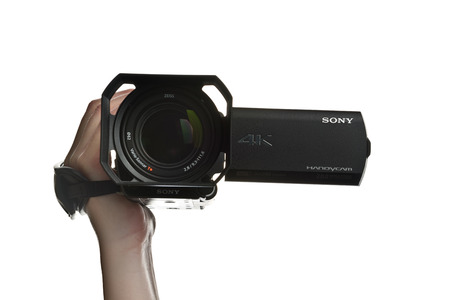 footage: NOVI SAD SERBIA  APRIL 25 2015: Person holding Sony FDR AX100 4k UHD Handycam Camcorder captures Ultra High Definition Footage. Illustrative editorial for product isolated on white background.