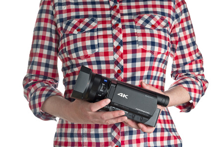 filming: NOVI SAD SERBIA  APRIL 25 2015: Person holding Sony FDR AX100 4k UHD Handycam Camcorder captures Ultra High Definition Footage. Illustrative editorial for product isolated on white background.