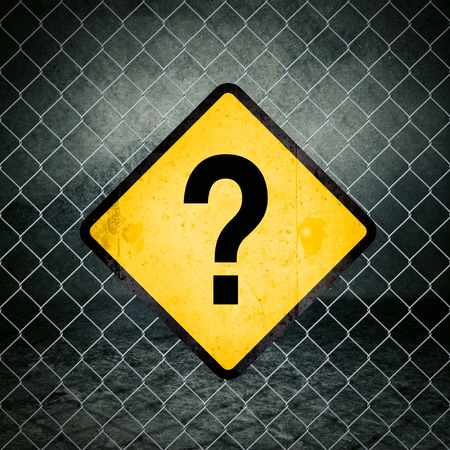 chainlink fence: Question Mark Grunge Yellow Warning Sign on Chainlink Fence of Industrial Warehouse Stock Photo