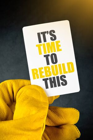 rebuild: Its Time to Rebuild on Business Card, Male Hand in Yellow Leather Construction Working Protective Gloves Holding Card. Stock Photo