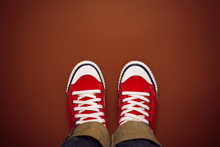 standpoint: Feet From Above Concept, Teenage Person in Red Sneakers Standing on Brown Background, Blank Copy Space in Front, Top View Stock Photo