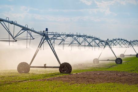 Geautomatiseerde Landbouw Irrigatie Sprinklers System in werking op Cultivated Landbouw Gebied Stockfoto