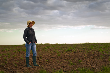 fertile land: Portrait of Adult Female Farmer Standing on Fertile Agricultural Farm Land Soil,Looking into Distance.