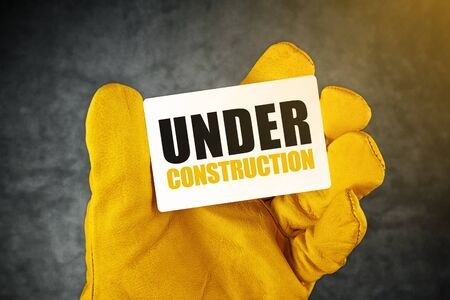 redesign: Under Construction on Business Card, Male Hand in Yellow Leather Construction Working Protective Gloves Holding Card with Rounded Corners. Stock Photo