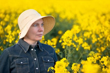 oilseed: Female Farmer Standing and Posing in Oilseed Rapeseed Cultivated Agricultural Field, Beauty Portrait Stock Photo