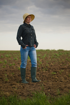 agricultural farm land: Portrait of Adult Female Farmer Standing on Fertile Agricultural Farm Land Soil,Looking into Distance.