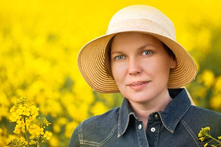 adult rape: Female Farmer Standing and Posing in Oilseed Rapeseed Cultivated Agricultural Field, Beauty Portrait Stock Photo