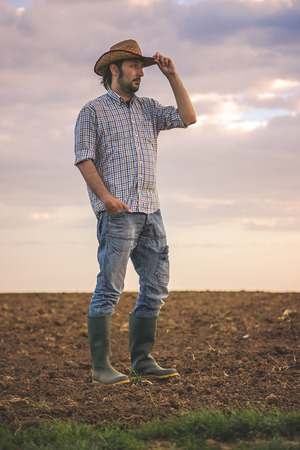 agricultural farm land: Portrait of Adult Male Farmer Standing on Fertile Agricultural Farm Land Soil,Looking into Distance. Stock Photo