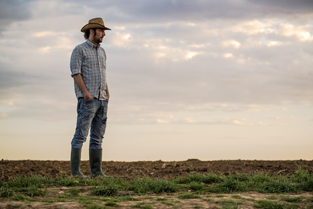 Portrait of Adult Male Farmer Standing on Fertile Agricultural Farm Land Soil,Looking into Distance. Stock Photo