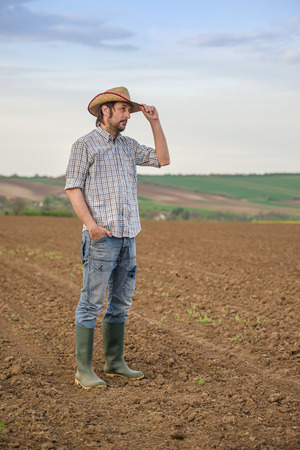 fertile land: Portrait of Adult Male Farmer Standing on Fertile Agricultural Farm Land Soil,Looking into Distance. Stock Photo