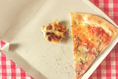 eaten: Pizza Slice and Fast Food Leftovers in Cardboard Box on Kitchen Table, Retro Style Toned Image, Selective Focus with Shallow Depth of Field