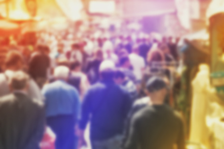 Blurred Crowd of People On Street, unrecognizable crowded population as blur urban background, Vintage Toned Image. Stock Photo