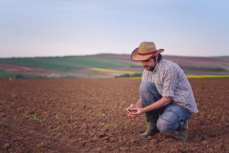 granjero: Granjero de sexo masculino examina la calidad del suelo en la fértil tierra agrícola Granja