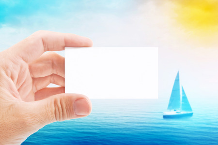 Tourist Agent Holding Blank Business Card, Sailboat at Sea in Background. photo