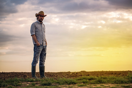 fertile land: Portrait of Adult Male Farmer Standing on Fertile Agricultural Farm Land Soil, Looking into Camera Stock Photo