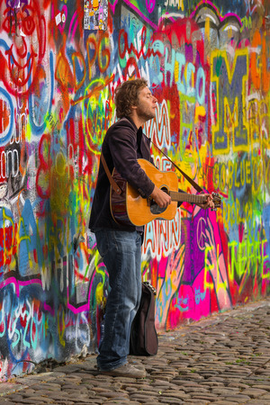busker: PRAGUE, CZECH REPUBLIC - MAY 21, 2015: Prague Street Busker Musician Performing Beatles Songs in Front of Famous John Lennon Wall on Kampa Island. Busking is Legal Form of Earning on Prague Streets. Editorial