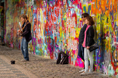 busker: PRAGUE, CZECH REPUBLIC - MAY 21, 2015: Prague Street Busker Musician Performing Beatles Songs in Front of Famous John Lennon Wall on Kampa Island. Tourist Couple posing for Photographer.