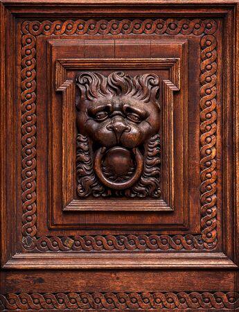 wood carving door: Lion Head as Wood Carving in Old Vintage Brown Massive Wooden Door Stock Photo