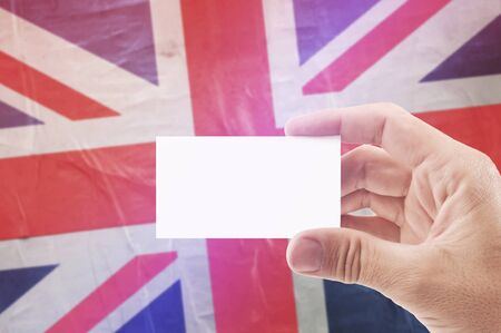 citizenry: Caucasian Man Holding Blank Business Card Against United Kingdom of Great Britain Flag, Retro Vintage Rustic Tone Effect