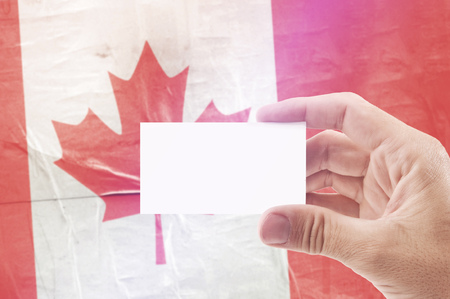 citizenry: Caucasian Man Holding Blank Business Card Against Canada National Flag, Retro Vintage Rustic Tone Effect Stock Photo