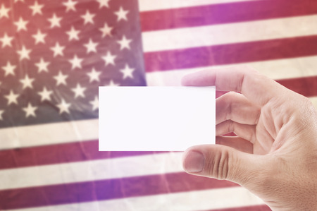 citizenry: Caucasian Man Holding Blank Business Card Against United States of America National Flag, Retro Vintage Rustic Tone Effect
