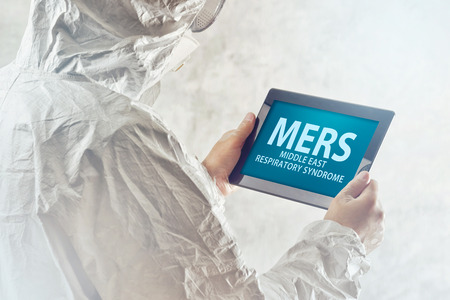 prevention of disease: Medical Scientist Reading Internet Pages About MERS Virus on Figital Tablet Computer Stock Photo