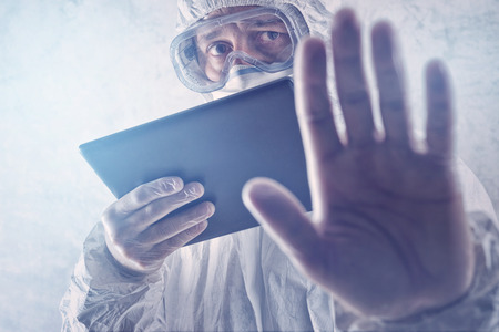 coronavirus: Medical Scientist Reading Internet Pages About MERS Virus on Figital Tablet Computer Stock Photo