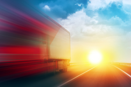 shipment: Speeding Transportation Delivery Truck on Open Highway with Sun Settimg Down on Horizon in Background. Stock Photo
