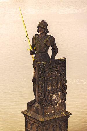 vltava: Sculptured Knight Brunswick (Bruncvik) Statue with Godlen Sword on Charles Bridge in Prague over River Vltava.