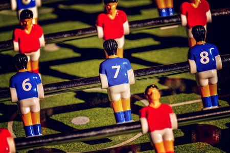 kicker: Vintage Foosball, Blue and Red Players Team in Table Soccer or Football Kicker Game, Selective Focus, Retro Tone Effect Stock Photo