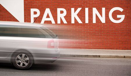 parking space: Parking Title on Brick Wall, Sign for Street Vehicle Parking Space, Motion Blurred Car Passing Stock Photo