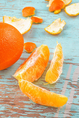 peel: Fresh Ripe Sweet Orange Tropical Fruit, Sliced Sections and Peel on Rustic Grunge Blue Wood Background