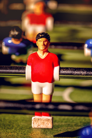 kicker: Single Player in Red Jersey, Vintage Foosball, Table Soccer or Football Kicker Game, Selective Focus, Retro Tone Effect Stock Photo