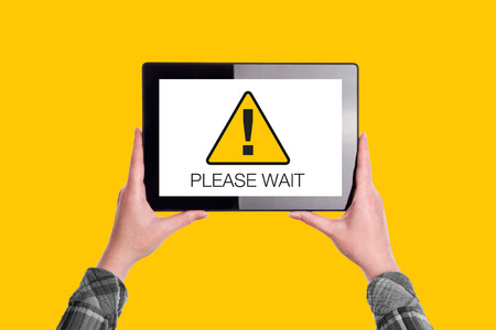 Please Wait Message on Digital Tablet Computer Display, Woman Holding Device, Isolated on Yellow Background Imagens
